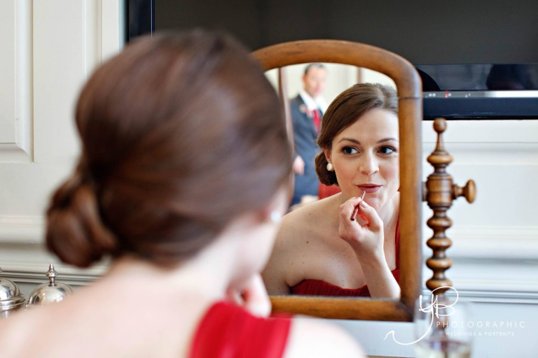 Bride in red makes the finishing touches to her make-up at Dean Street Townhouse.