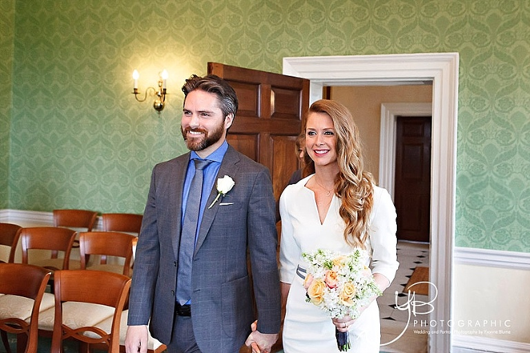 The smiling bride and groom enter the Sheraton Room in Morden Park House for their civil marriage ceremony in front of family and friends.