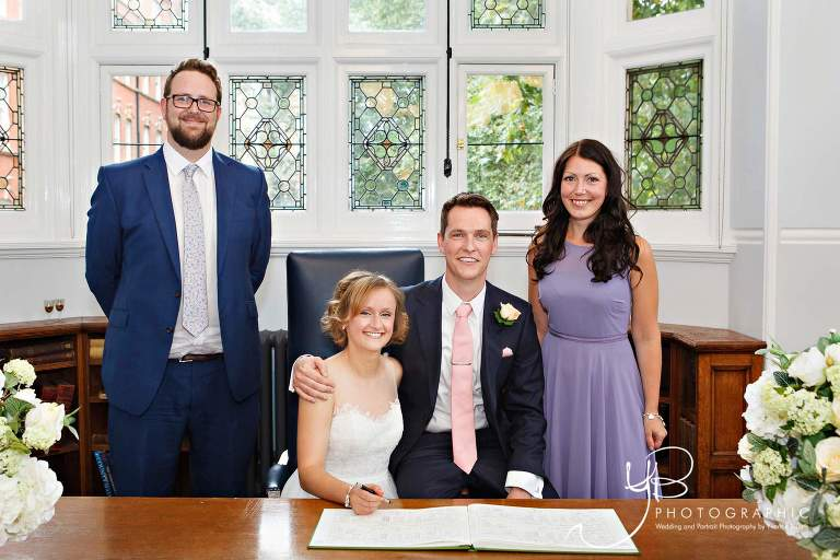 The bride and groom pose with their witness after signing the register