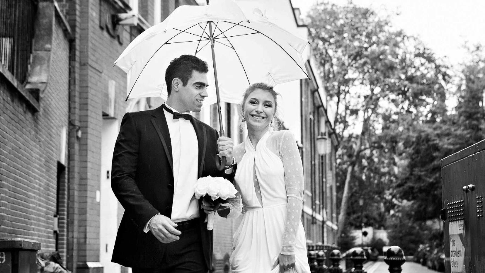 A bride and groom pose under a white umbrella for wedding portraits after their Chelsea wedding. The groom is holding the bride's bouquet for their wedding photos.