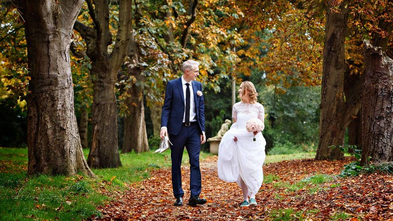 A bride and groom walk through the woods after their autumn wedding ceremony. They were making the most of the warm autumn colours for their wedding photos.