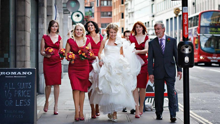 A bride walks through London's streets with her four bridesmaids dressed in red, carrying red and orange bouquets. She was on the way to her wedding. Photo: London wedding photographer Yvonne Blume.