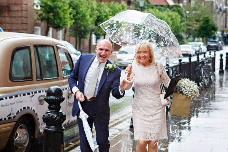 Fun bride and groom in the rain at their elopement with Chelsea Pensioners as their witnesses.