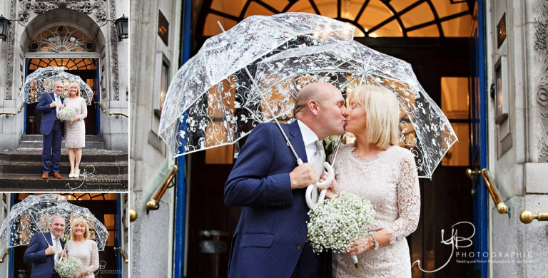 An eloping couple stand on the Kings Road after their civil marriage ceremony, ignoring the rainy weather.