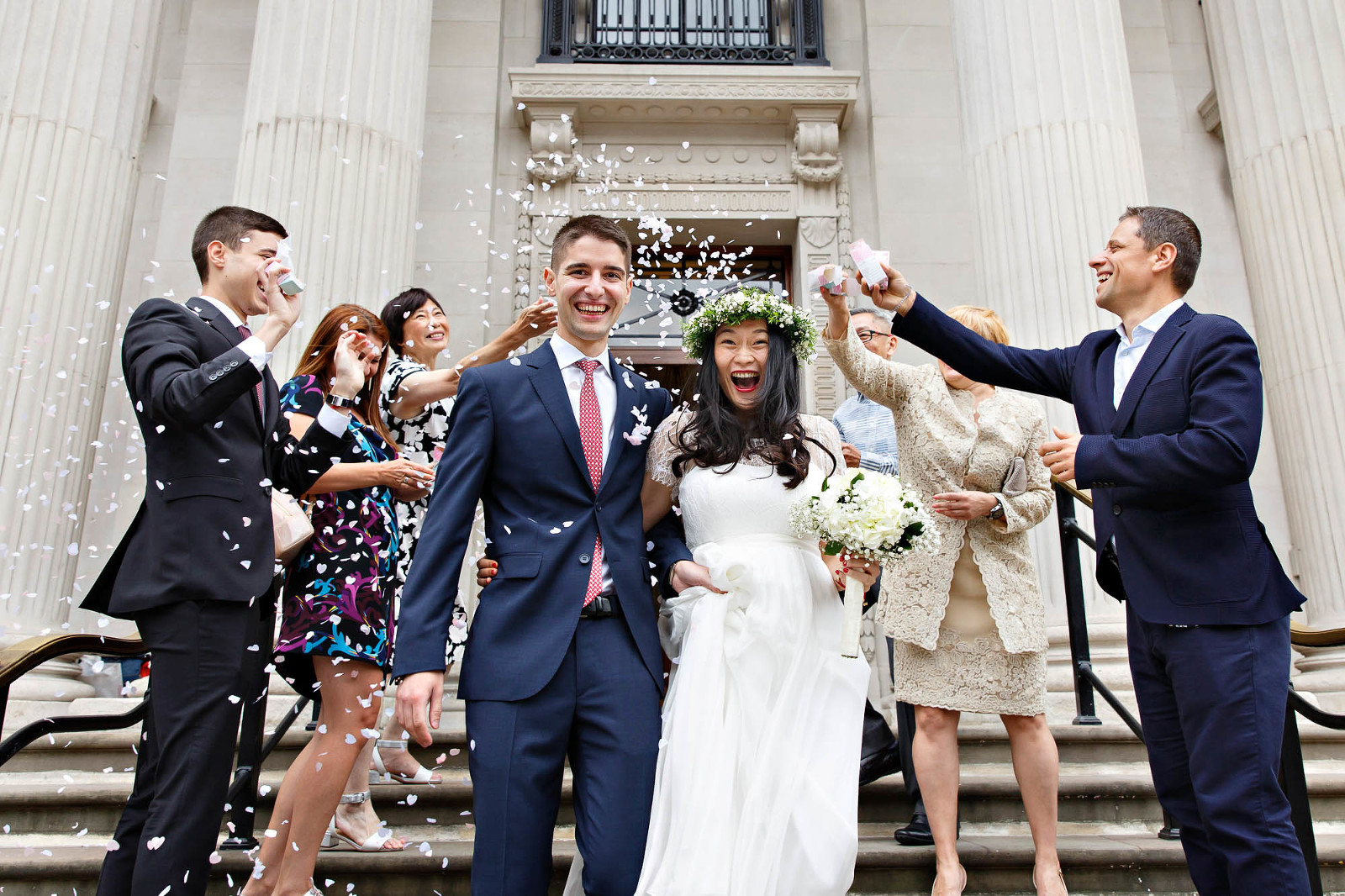 Newlyweds descend the steps of Old Marylebone Town Hall after their civil marriage ceremony.