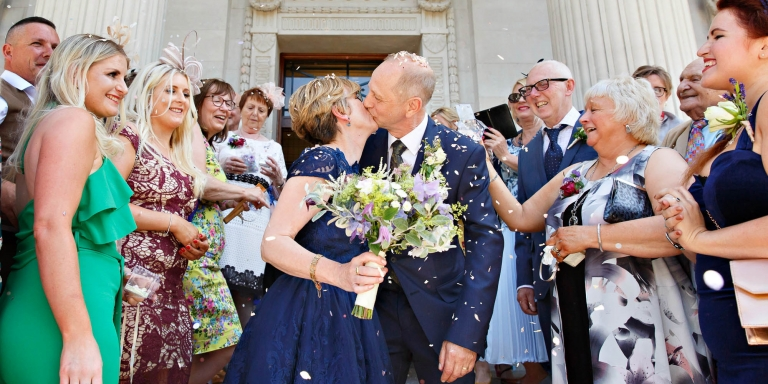 A newlywed couple kiss on the steps of Old Marylebone Town Hall after their civil marriage ceremony in Westminster Register Office. They're surrounded by family and friends wishing them every happiness.