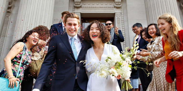 A newlywed bride and groom on the steps of Old Marylebone Town Hall after their civil marriage ceremony in front of Westminster City registrars.