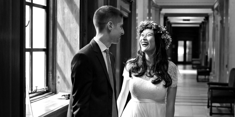 Black and white photo of couple in one of the corridors of Old Marylebone Town Hall before their civil wedding ceremony. The town hall is the home of Westminster Register Office and has seven ceremony rooms for civil marriage ceremonies and civil partnership ceremonies.