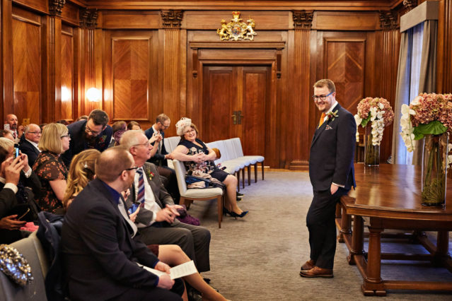 A groom waits in the Westminster Room at Old Marylebone Town Hall with his guests, awaiting the arrival of his bride. The Westminster Room seats up to 100 guests in a wood-panelled room.