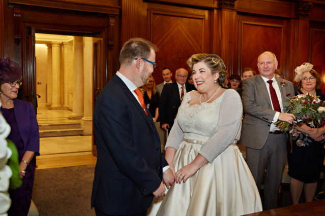 The groom welcomes his bride when she arrives at their ceremony in the Westminster Room at Old Marylebone Town Hall in the City of Westminster, London.