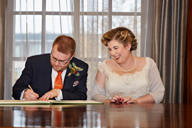 The bride and groom sign the register during their civil marriage ceremony at Old Marylebone Town Hall in the Westminster Room.