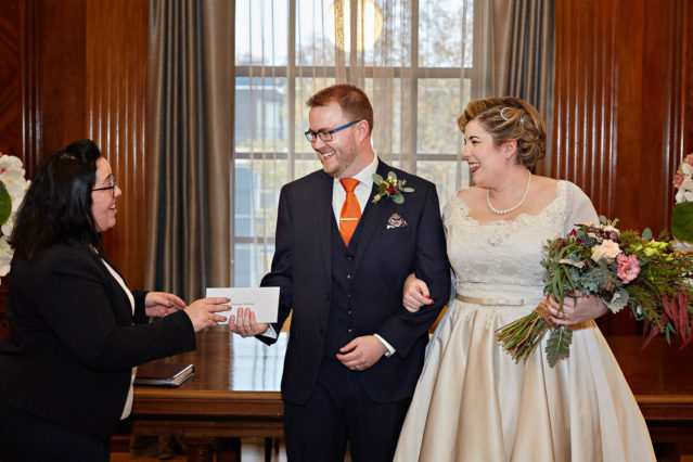 The bride and groom receive their marriage certificate after their civil marriage ceremony in the Westminster Room at London's Old Marylebone Town Hall.