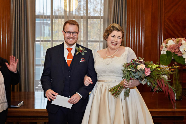 The bride and groom pose for photos in the Westminster Room at Old Marylebone Town Hall. The bride is wearing a vintage cream 1950s style wedding dress with a full skirt and lace bodice.