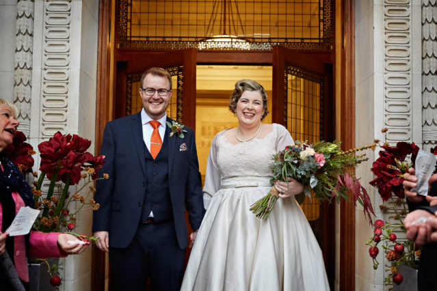 A vintage-style bride stands outside Old Marylebone Town Hall with her new groom after their registry office wedding ceremony in the Westminster Room.