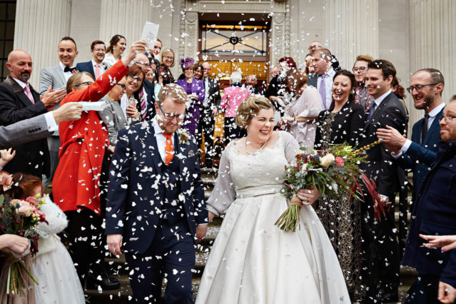 A vintage-style 1950s style bride and her groom are enveloped in confetti on the steps of Old Marylebone Town Hall.