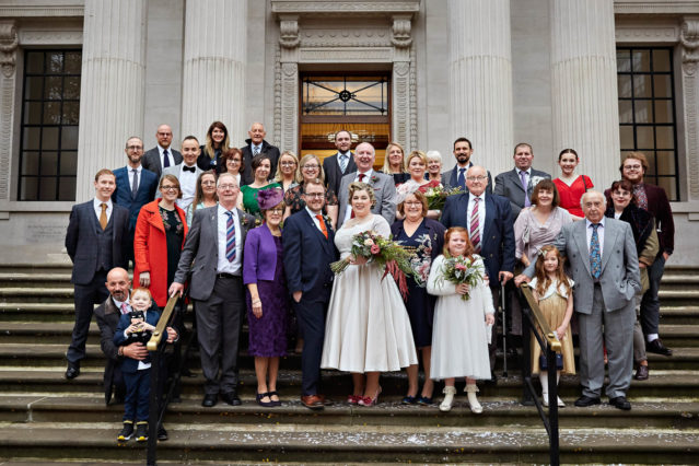 A family group stands on the steps of Westminster Registry Office - Old Marylebone Town Hall on Marylebone Road, London, after a civil marriage ceremony.