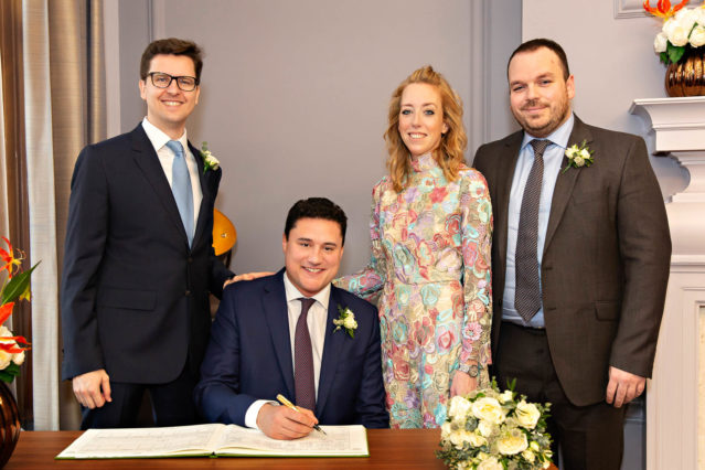 The bride, groom and their two witnesses sign the register after a civil marriage ceremony in the Knightsbridge Room in Westminster's Old Marylebone Town Hall.