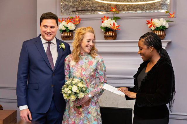 A bride dressed in a floral wedding dress and her groom dressed in a blue suit receive their marriage certificate from a Westminster registrar in London.