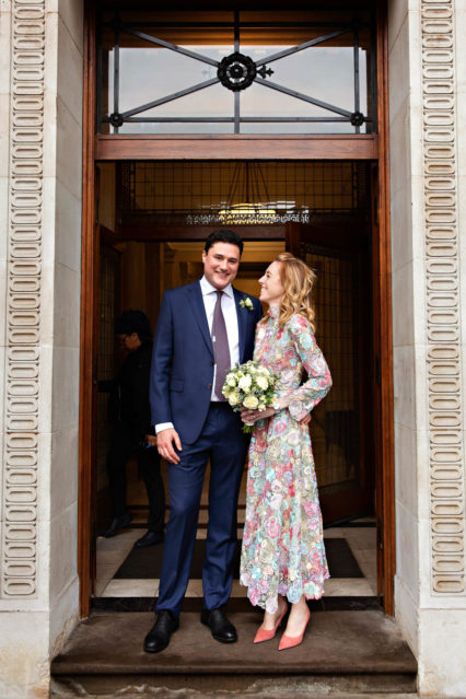 Two newlyweds stand in the front door of Old Marylebone Town Hall on Marylebone Road, London N1.