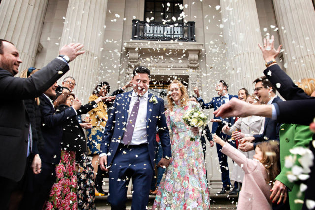 Confetti envelops the bride and groom on the steps of Old Marylebone Town Hall in London N1.