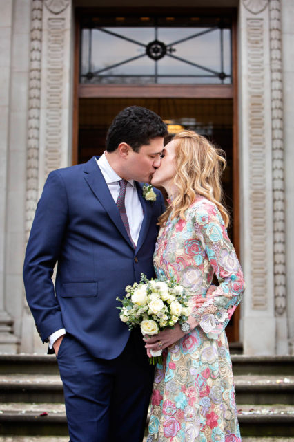 A bride and groom kiss on the steps of the town hall on Marylebone Road, London.