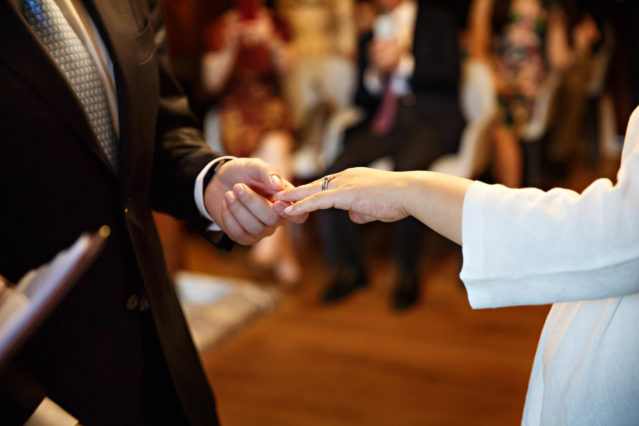 An exchange of rings during the civil wedding ceremony in the Marylebone Room.