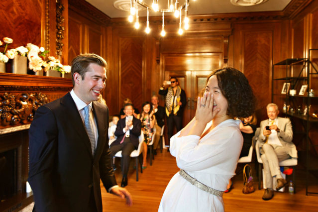 A Marylebone Room wedding ceremony: the bride and groom giggle in a lighthearted minute.