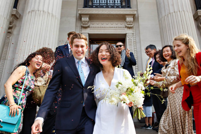 A bride and groom leave Old Marylebone Town Hall after their registry office wedding ceremony in the Marylebone Room.