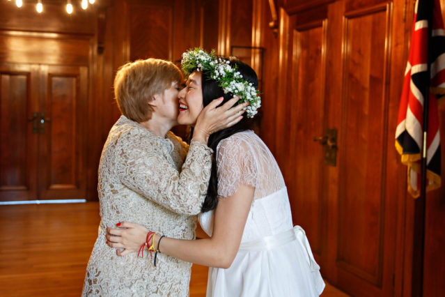 A bride and her future mother in law embrace before a civil wedding ceremony in the Marylebone Room.