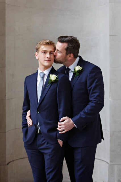 Wedding portraits of two grooms outside Old Marylebone Town Hall in London.