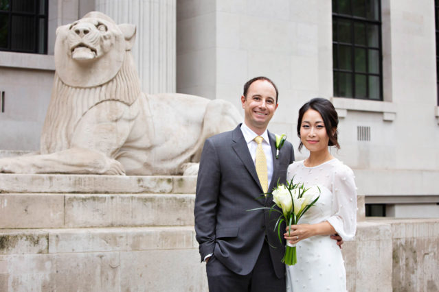 A bride and groom stand near the stone lions outside Old Marylebone Town Hall before their ceremony in the Marylebone Room.