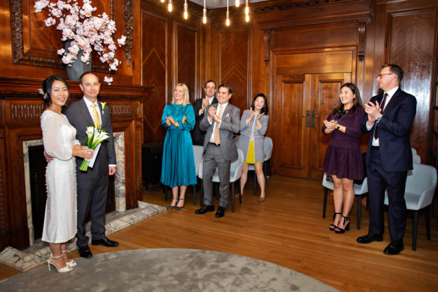 The bride and groom stand in front of their guests in the Marylebone Room.
