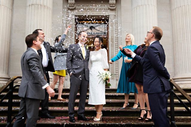 Confetti whirls around two newlyweds after their Marylebone Room marriage ceremony. They're on the steps of Old Marylebone Town Hall.