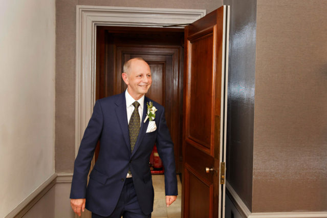 A groom in a blue suit and tie enters the Mayfair Room, ready to get married.