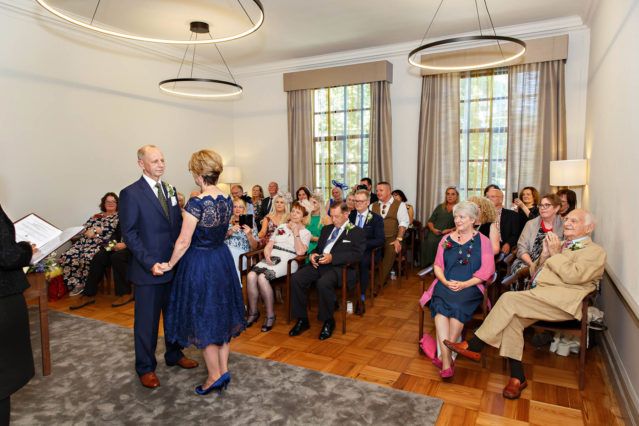 Guests watch the bride and groom exchange vows in front of their guests in the Mayfair Room at Marylebone Old Town Hall.