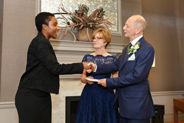 A Westminster marriage registrar hands over a wedding certificate to the bride and groom after their Mayfair Room civil marriage ceremony.