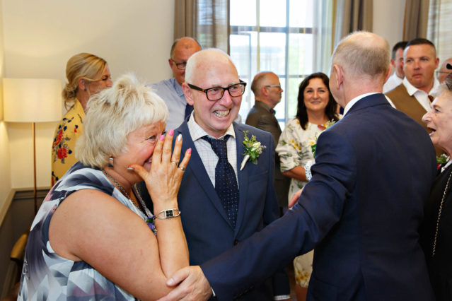 Guests congratulate the groom after a civil marriage ceremony in the Mayfair Room in London's Old Marylebone Town Hall.