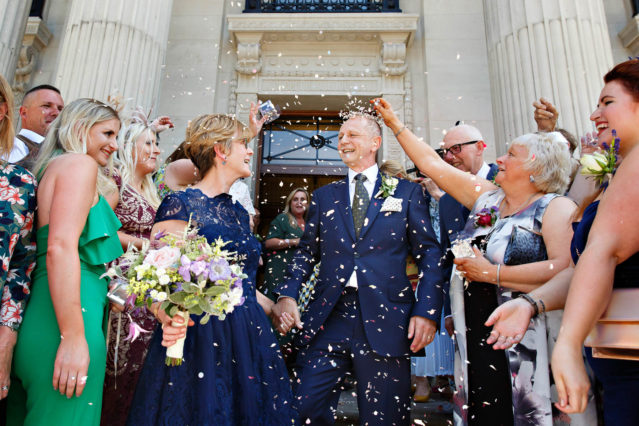 A bride in a blue lace cocktail dress holding a white bouquet and her groom wearing a navy suit and tie are congratulated by their guests on the steps of Old Marylebone Town Hall.
