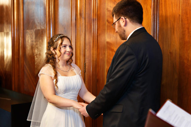 The bride and groom exchange vows during a registry office wedding in the Paddington Room.