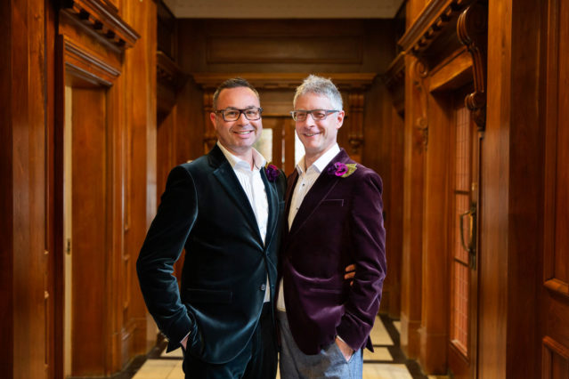 Two grooms in jewel coloured velvet suit jackets pose for a portrait outside the Paddington Room in Marylebone Town Hall in central London.