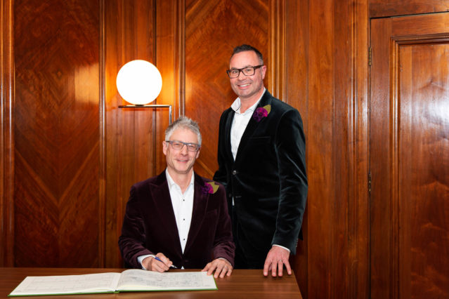 Two grooms sign the register that is the official paperwork of their civil wedding ceremony in the Paddington Room, in London's Marylebone.