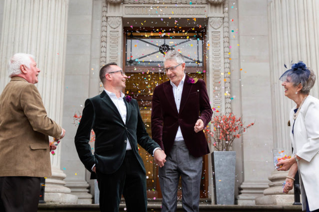 A gay couple walks down the steps of Old Marylebone Town Hall after their register office wedding ceremony in front of two witnesses.