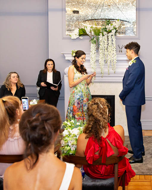 A bride in a colourful dress exchanges vows with her groom in a navy suit in the Knightsbridge Room in London's Westminster City.