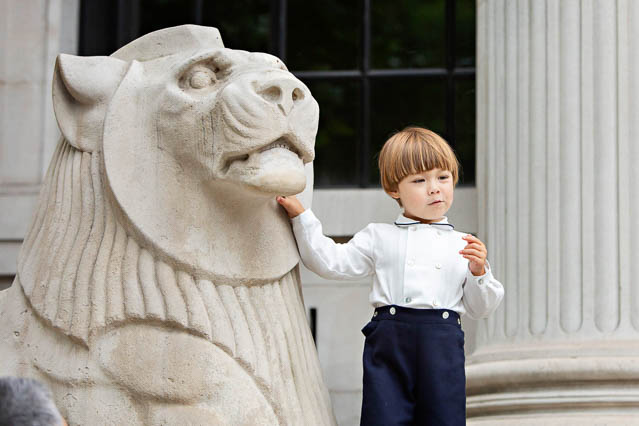 The son of the bride and groom stands next to the Portland Stone lion of Marylebone Old Town Hall.