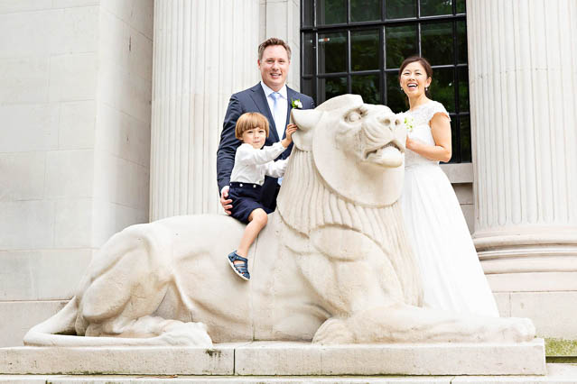 A bride, groom and their son stand near Marylebone Old Town Hall's stone lion.