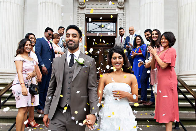 Yellow and white confetti whirls around the heads of the bride and groom on the steps of Old Marylebone Town Hall.