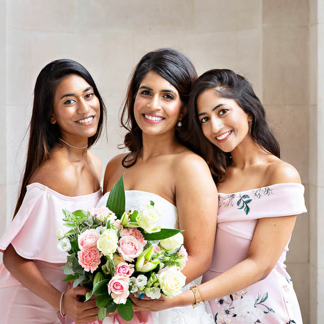 The bride and two of her best friends pose for wedding photos outside Marylebone Old Town Hall in central London.