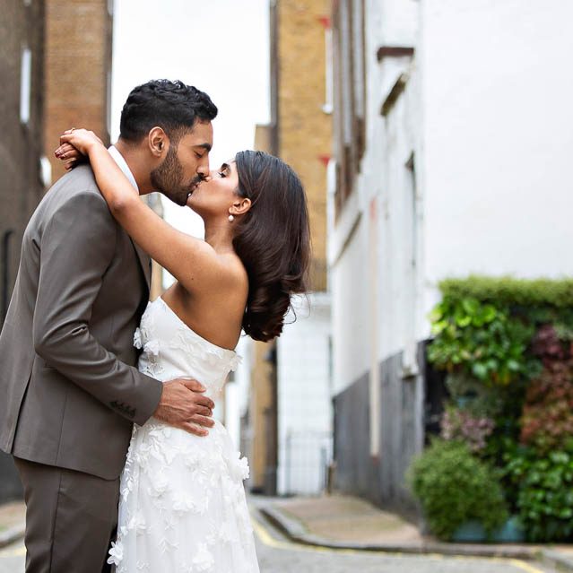 The bride and groom kiss during their Marylebone wedding portrait session.