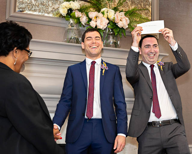 Two grooms hold up their wedding certificate after their small wedding in the Mayfair Room, Marylebone.
