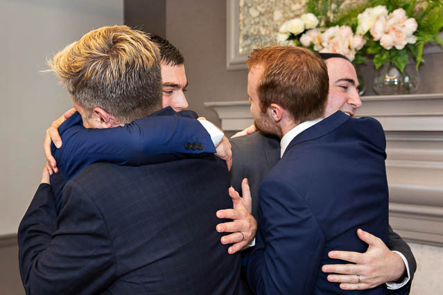 Two grooms hug their guests after getting married in the Mayfair Room at Old Marylebone Town Hall.